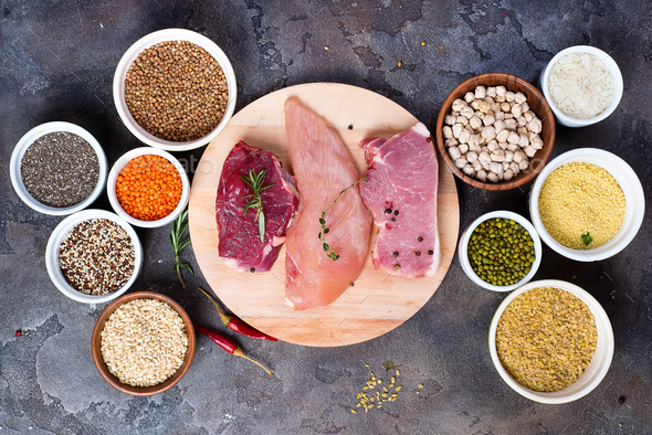 Raw food beef meat and chicken breast with cereals in bowl on stone dark background, flat lay - Stock Photo - Images
