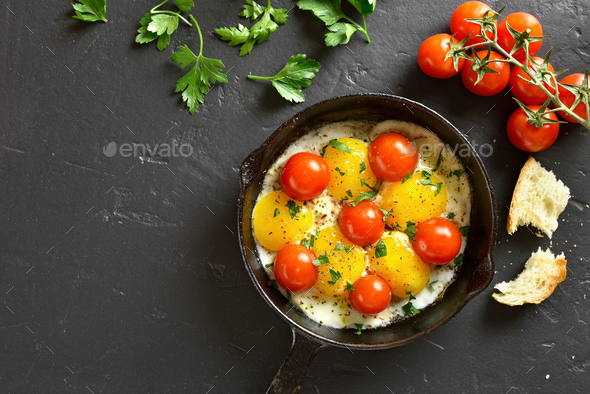Fried eggs with tomatoes in frying pan - Stock Photo - Images