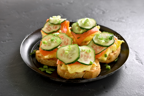 Sandwiches with salmon, scrambled eggs and cucumber - Stock Photo - Images