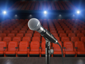 Microphone on the stage of concert hall or theater with red seat