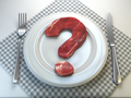 Plate with raw meat in the shape of a question mark. Concept of