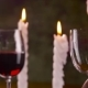 Male Hand Pouring Red Wine in Glass From Bottle on Candle Background - VideoHive Item for Sale