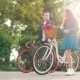 Beautiful Young Couple Walking with Bicycles in Green Spring Park and Talking To Each Other - VideoHive Item for Sale