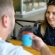 Young Man Takes a Glass of Coffee From His Lover and Drinks From It. The Girl Is Surprised at the - VideoHive Item for Sale
