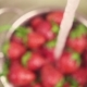 A Stream of Water Pours into a Colander with Strawberries - VideoHive Item for Sale