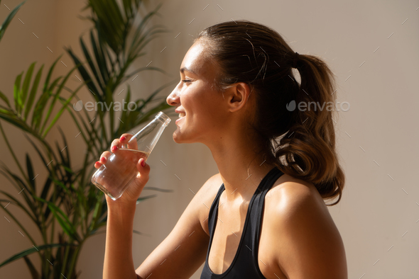sporty woman drinking water - Stock Photo - Images