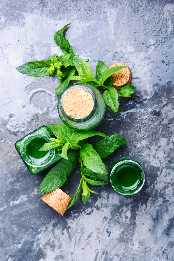 Essential mint oil with green leaves - Stock Photo - Images