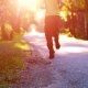 Sport Man Running at Asphalt Road. Rural City Park. Green Tree Forest and Sun Rays on Horizon. - VideoHive Item for Sale