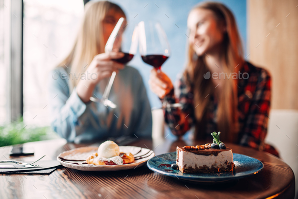 Girlfriends drinks red wine and eats dessert - Stock Photo - Images