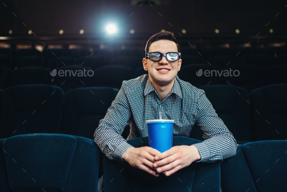 Teenager in 3d glasses holds beverage in cinema - Stock Photo - Images