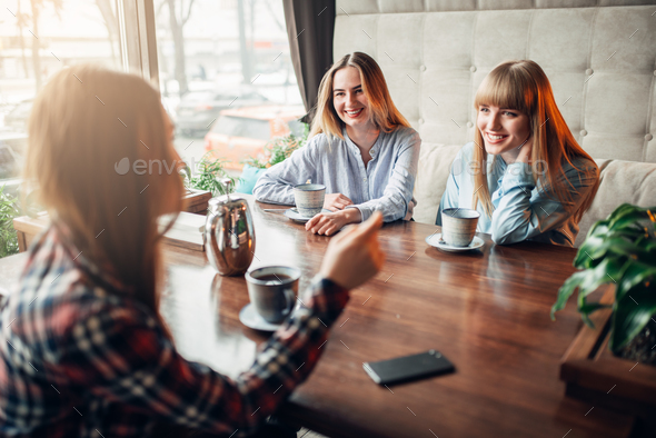 Happy girlfriends drinks coffee at the table - Stock Photo - Images
