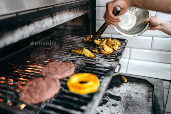 Male cook prepares grilled potato - Stock Photo - Images