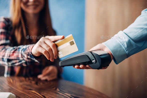 Young woman paying with credit card in cafe - Stock Photo - Images