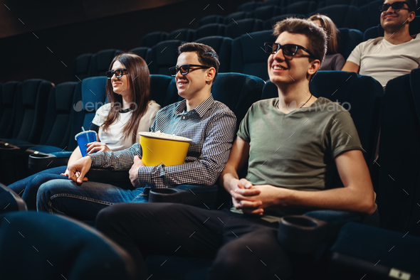 People with popcorn watching movie in cinema - Stock Photo - Images