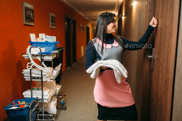 Housemaid in uniform knocking on the room door - Stock Photo - Images