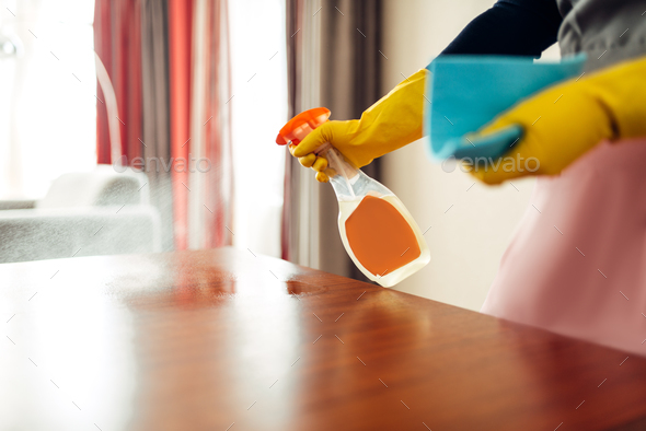 Housemaid hands cleans table with cleaning spray - Stock Photo - Images