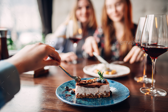 Young women eats sweet cakes in restaurant - Stock Photo - Images