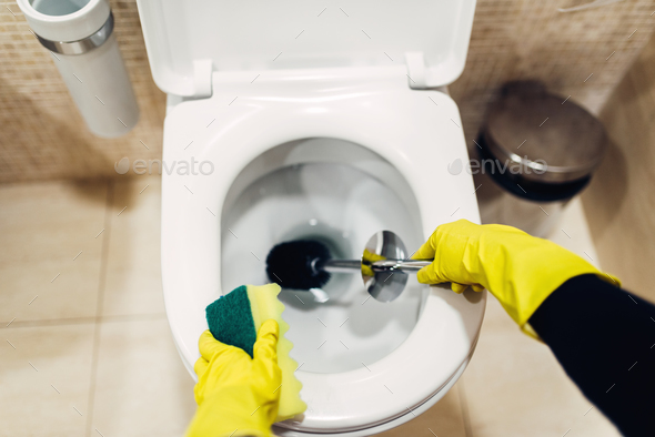 Housemaid in gloves cleans the toilet with brush - Stock Photo - Images
