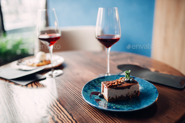 Dessert on plate and red wine in glass, nobody - Stock Photo - Images