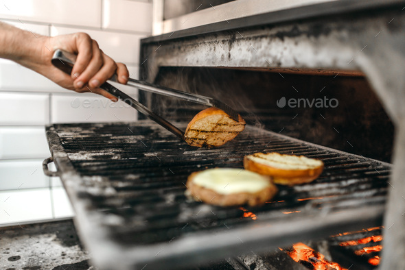Male cook prepares tasty meat on grill oven - Stock Photo - Images