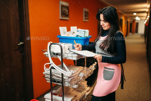 Cute maid makes notes after cleaning the room - Stock Photo - Images