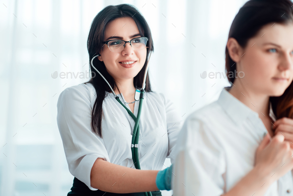 Doctor listens to patient using a stethoscope - Stock Photo - Images