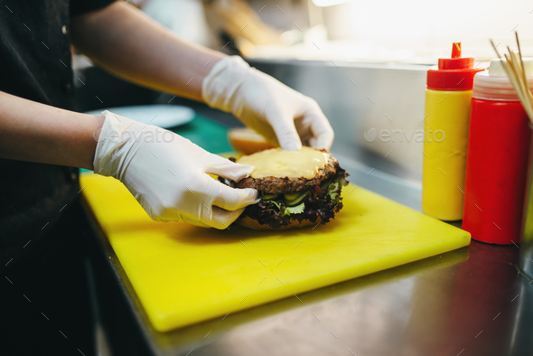 Male cook prepares fast food, burger preparation - Stock Photo - Images