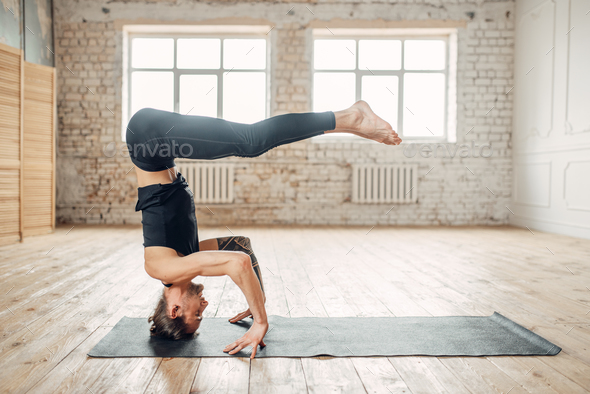 Male yoga stands on the head in gym - Stock Photo - Images
