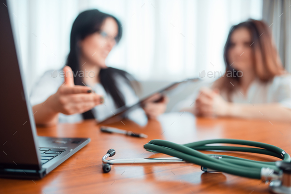 Family doctor, young wife talks with specialist - Stock Photo - Images