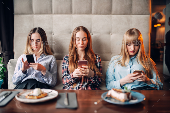 Three girls using mobile phones in cafe - Stock Photo - Images