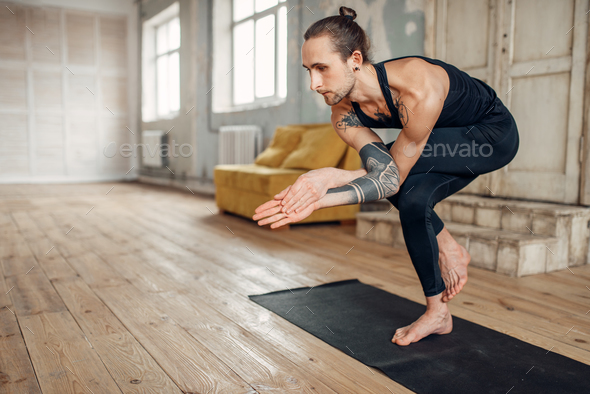 Male yoga doing balance exercise on mat in gym - Stock Photo - Images