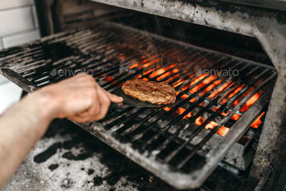 Cook hands prepares smoky meat on grill oven - Stock Photo - Images