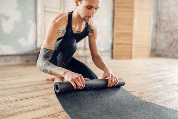 Male yoga with tattoo prepares mat for training - Stock Photo - Images
