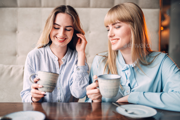 Two smiling girlfriends drinks coffee in cafe - Stock Photo - Images