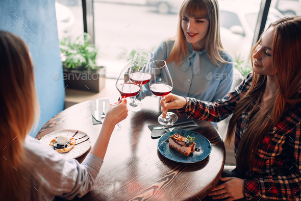 Three girlfriends holding beverages in glasses - Stock Photo - Images