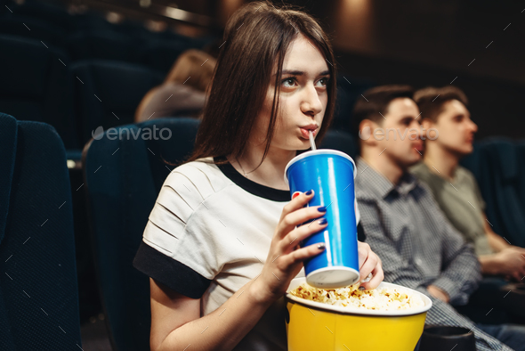 Woman with beverage and popcorn sitting in cinema - Stock Photo - Images