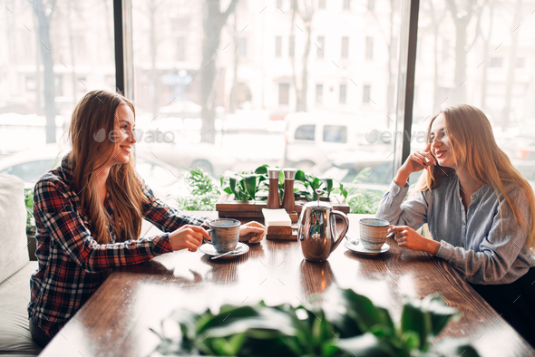 Two girlfriends met in a cafe to drink coffee - Stock Photo - Images