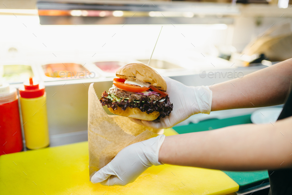 Chef puts burger in to the cardboard package - Stock Photo - Images