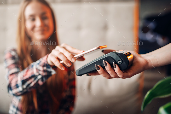 Young woman pay by mobile phone in cafe - Stock Photo - Images