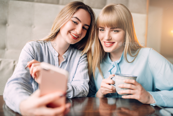 Young woman shows photos to her girlfriend in cafe - Stock Photo - Images
