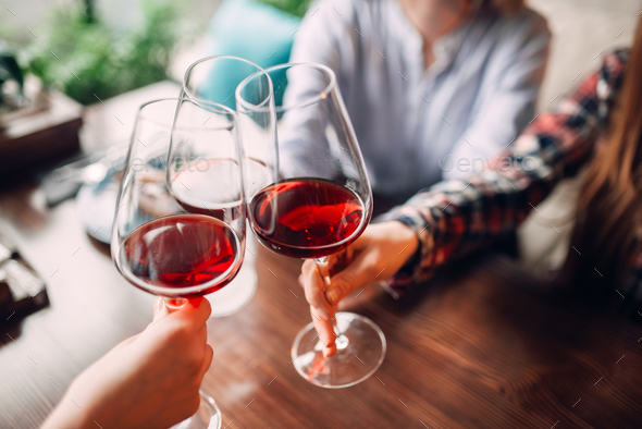 Girlfriends clink glasses with red wine - Stock Photo - Images