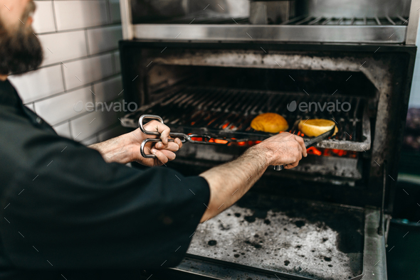 Male cook prepares tasty burger on grill oven - Stock Photo - Images