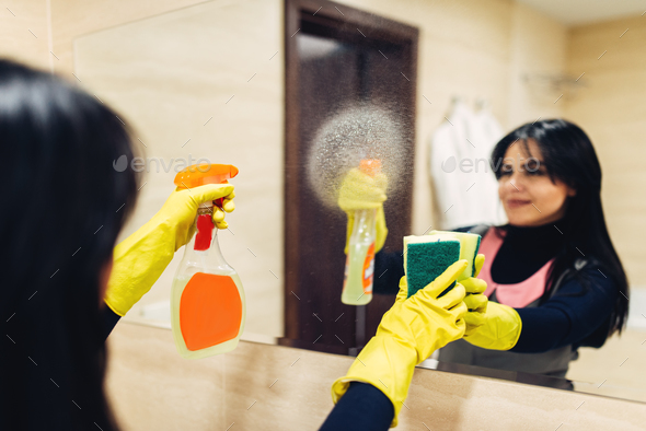 Housemaid cleans the mirror with a cleaning spray - Stock Photo - Images