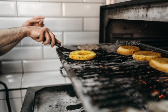 Smoky meat and ingredients grilling for burgers - Stock Photo - Images