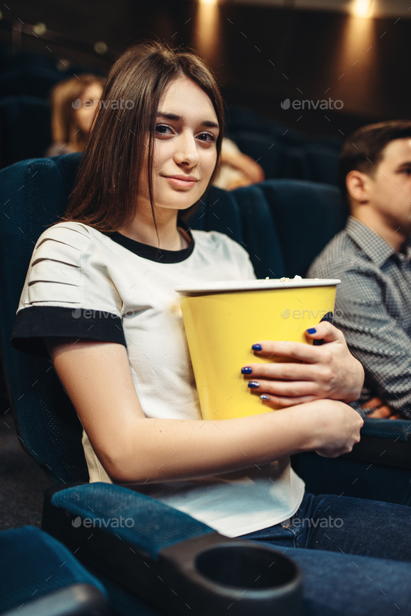 Woman eats popcorn while watching movie in cinema - Stock Photo - Images