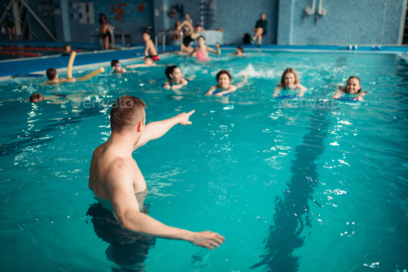 Instructor works with class in swimming pool - Stock Photo - Images