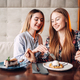 Two chicks drinks beverages and eats cakes in cafe - PhotoDune Item for Sale