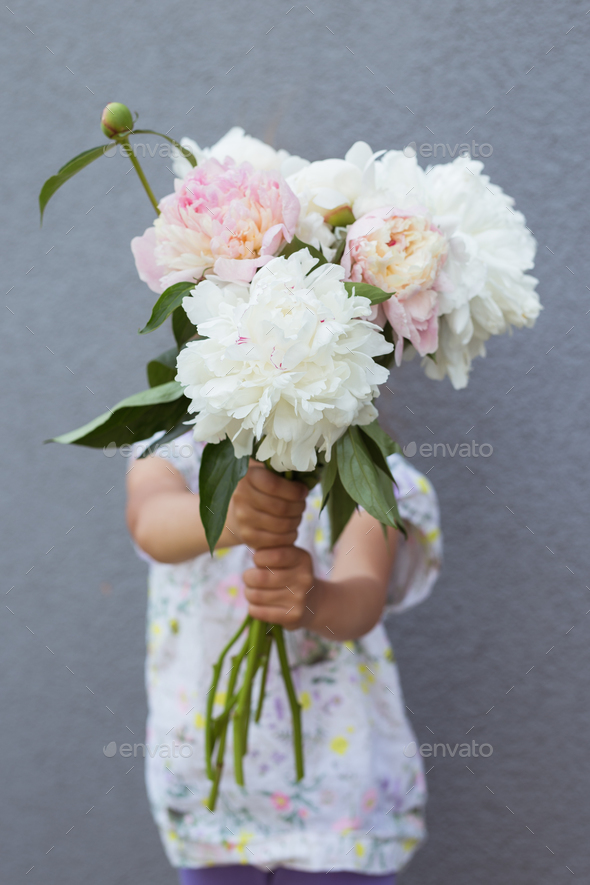 Portrait of a beautiful little girl with a bouquet of peonies - Stock Photo - Images