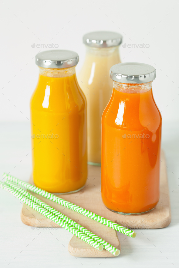 fruit and vegetable smoothies in glass jars, orange mango banana - Stock Photo - Images