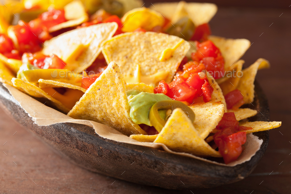 nachos loaded with salsa, guacamole, cheese and jalapeno - Stock Photo - Images